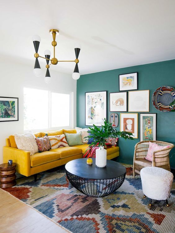 a colorful eclectic living room with a green statement wall with artworks, a boho rug, a mustard sofa and wicker touches