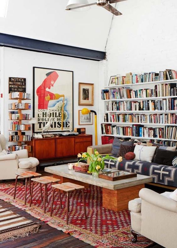 a colorful eclectic living room with open bookshelvesm bright printed textiles, neutral furniture and touches of mid-century modern