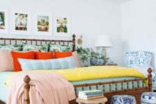 a colorful eclectic sleeping space with a bamboo bed, a gallery wall with holiday photos, elegant blue and white side tables and a bead chandelier