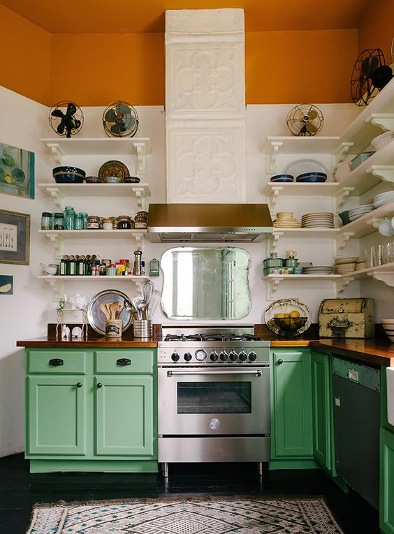 a colorful vintage meets rustic kitchen with a tiled hood, a rust stripe, green cabinets and white shelves