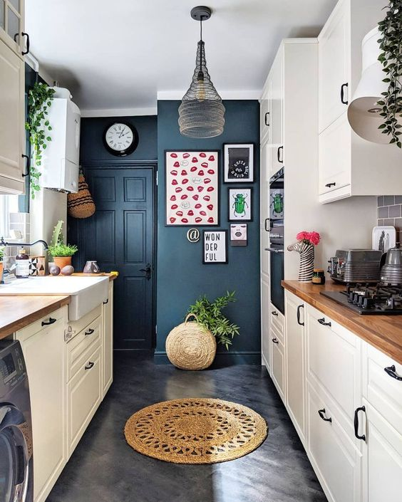 a contemporary kitchen with navy walls, white cabinets with wooden countertops and a catchy pendant lamp