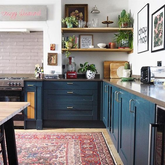a contemporary meets boho kitchen with a boho rug, navy cabinets, a stone countertop and potted plants