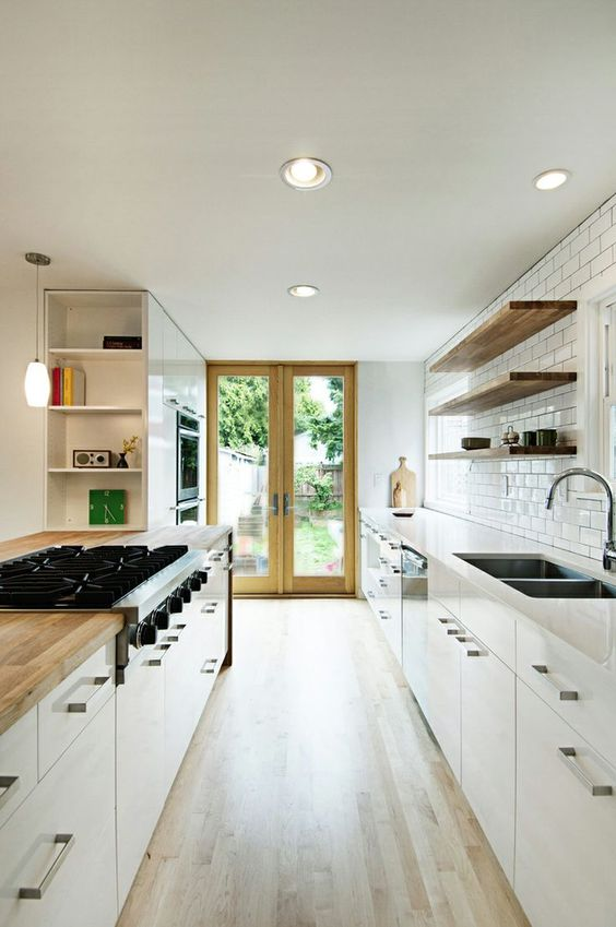 a contemporary neutral galley kitchen with white cabinets and butcher block countertops plus a white subway tile backsplash