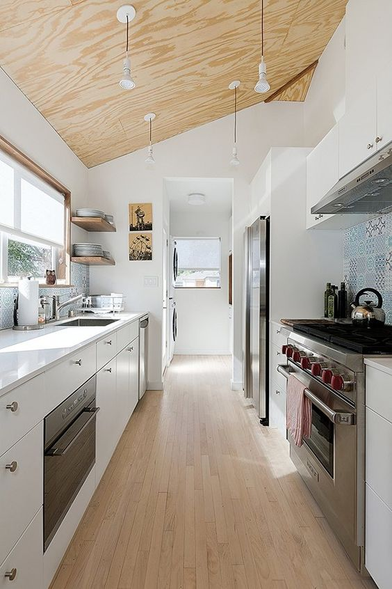 a contemporary white galley kitchen with a plywood ceiling with penddant lamps, a wooden floor and a blue tile backsplash