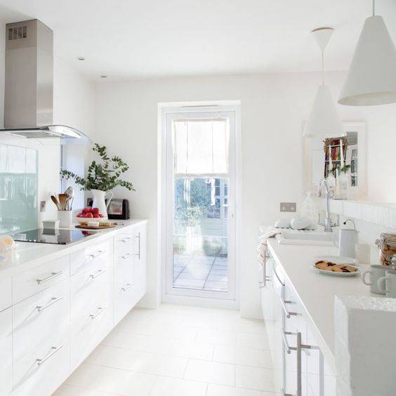 a contemporary white galley kitchen with white cabinets, metal and glass touches and an access to the terrace with much light