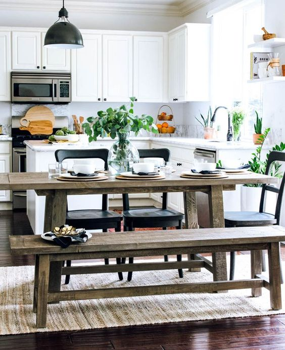 a fresh contemporary kitchen in white with a rustic dining zone with benches and touches of blakc for drama