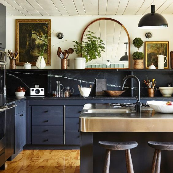 a gorgeous eclectic kitchen combining stone backsplash and countertops, navy cabinets and vintage artworks and a mirror