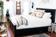 a light-filled eclectic bedroom with a dark bed, a rustic ladder for storage, prints, glam tables and potted greenery