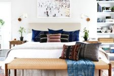 a light-filled eclectic bedroom with an upholstered bed, a woven bench, built-in shelves, wooden nightstands and potted greenery