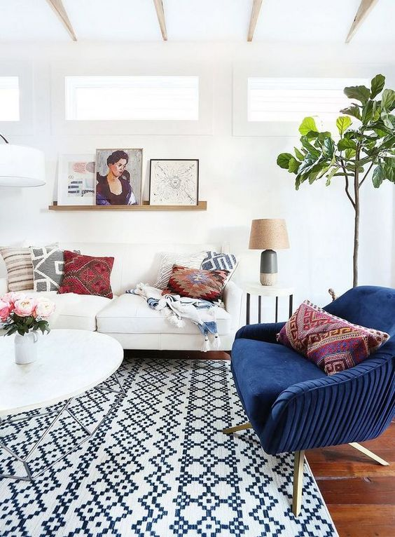 a light-filled eclectic living room with several geometric prints, a navy chair, potted greenery and artworks