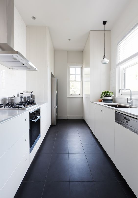 a minimalist white galley kitchen with sleek cabinets,pendant lamps and a black tile floor for a contrast