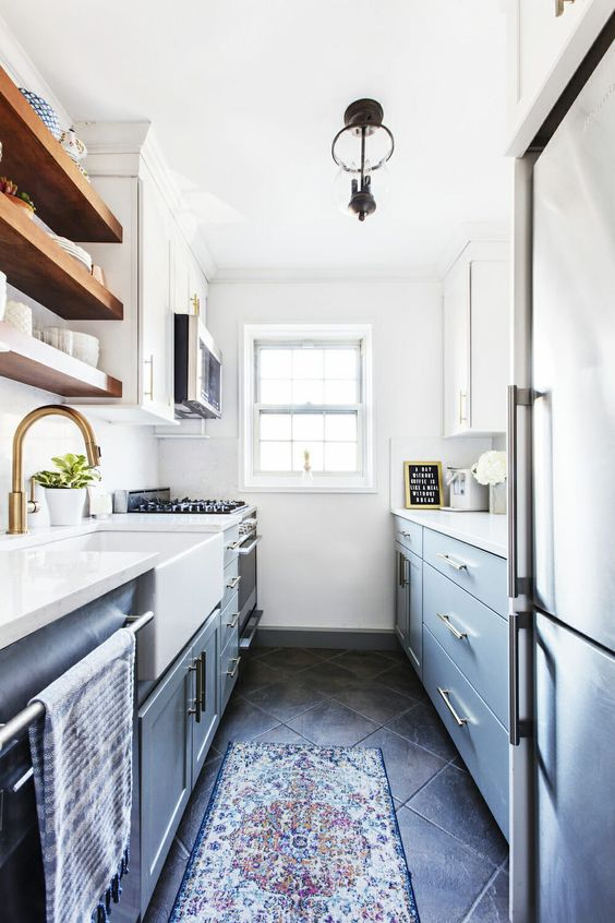 a modern farmhouse galley kitchen in light blue and navy, with white countertops, brass touches and wooden shelves