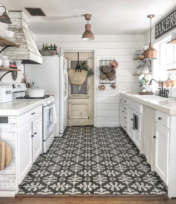 a modern farmhouse galley kitchen with white cabinets, blakc hardware, a mosaic floor and a wooden hood