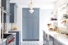 a modern farmhouse kitchen in powder blue with a mosaic tile floor, elegant pendant lamps and gilded touches for more elegance