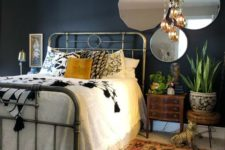 a moody eclectic bedroom with boho rugs and a chandelier, vintage mirrors and a metal bed and mid-century modern nightstands