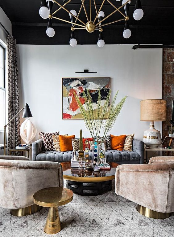 a moody eclectic living area with a black ceiling, colorful pillows, velvet chairs and a brass chandelier