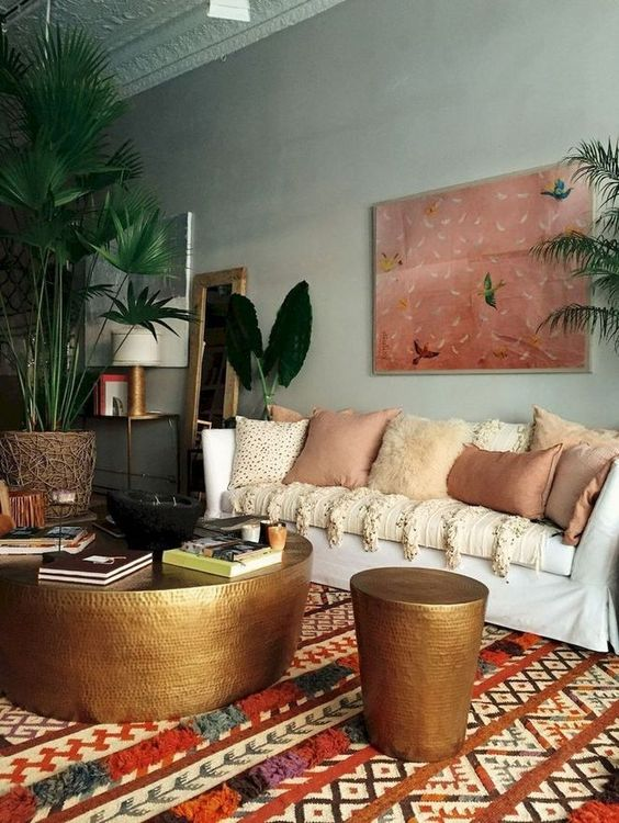 a moody eclectic space with a statement artwork, a boho printed rug, lots of earthy pillows and metal hammered items