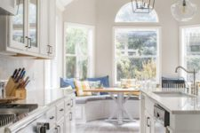 a neutral farmhouse galleykitchen with chic cabinets and white stone countertops, a wooden floor and catchy pendant lamps