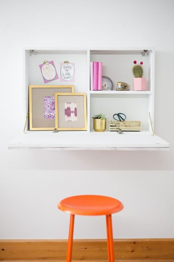 a simple white Murphy desk with some storage space inside and a large desktop is a comfortable workspace