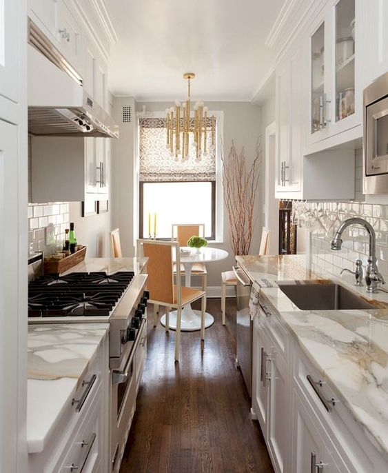 a small and welcoming galley kitchen with white cabinets and white stone countertops, a cozy dining space wth a round table and a glam chandelier