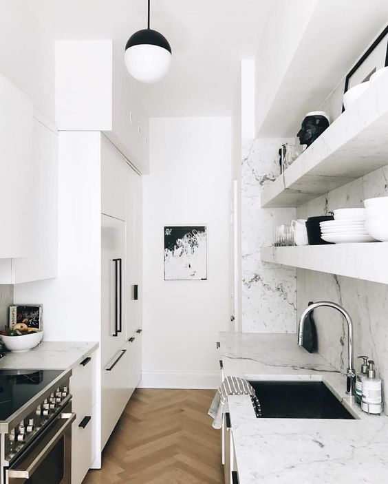 a small white Scandinavian kitchen with white marble countertops and backsplash plus black touches