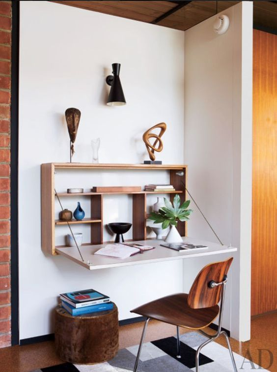 a stylish Murphy desk with a stained plywood base and a white desktop plus some display shelves inside and some artworks on top