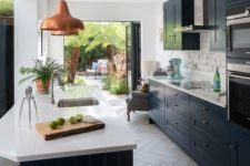 a stylish galley kitchen with navy cabinets and white stone countertops, copper pendant lamps and a brick backsplash