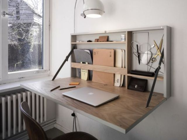 a stylish modern Murphy desk with a grey base and a stained plywood desktop plus some minimal storage space inside