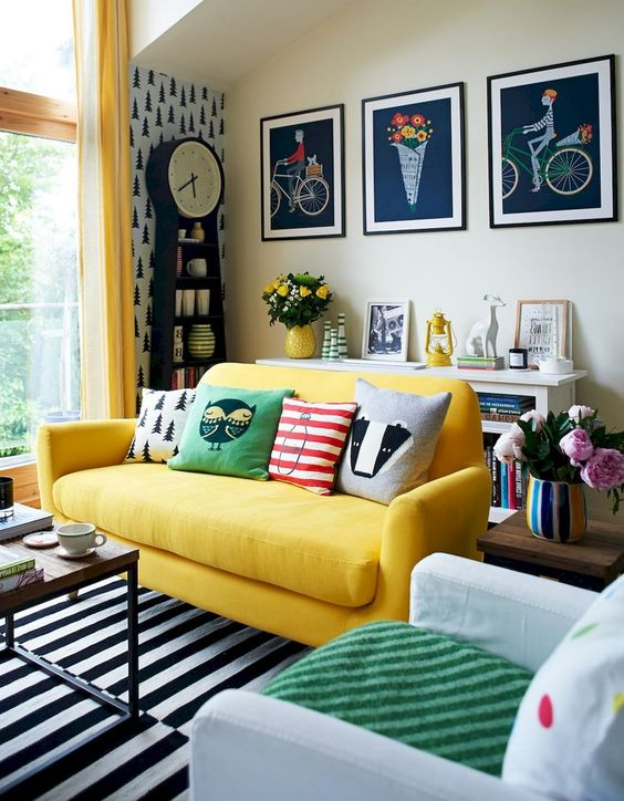 a super colorful eclectic living space with a symmetric living room, a yellow sofa, lots of prints and a contemporary coffee table