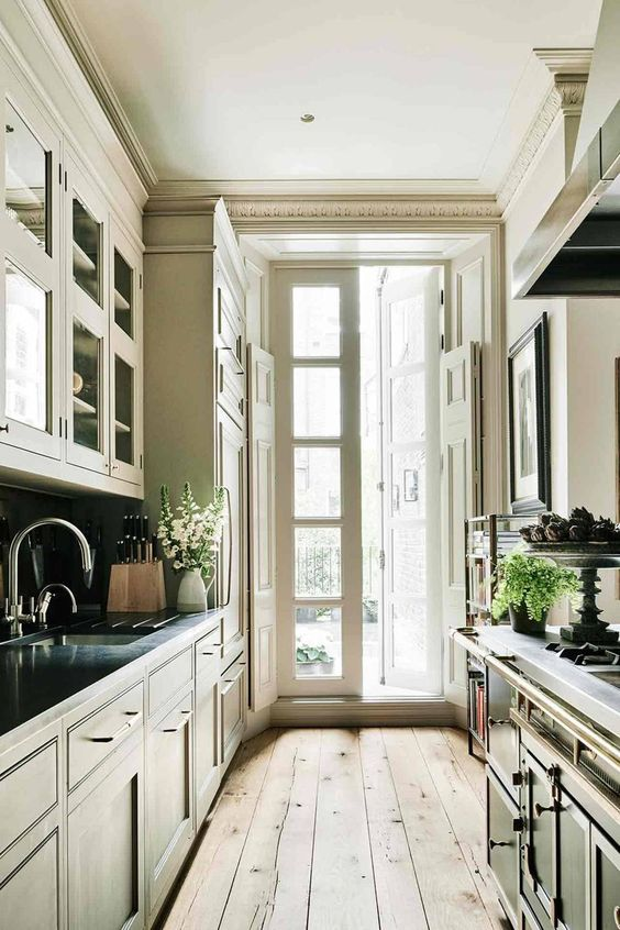 a traditional galley kitchen with vintage dark cabinets, a wooden floor, an access to the balcony with much natural light