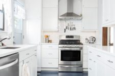 a tranquil neutral galley kitchen with white cabinets and countertops, a navy floor and stainless steel appliances