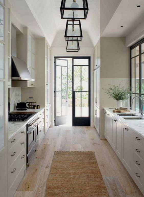 a vintage-inspired galley kitchen with white cabinets, white stone countertops and touches of blakc for drama