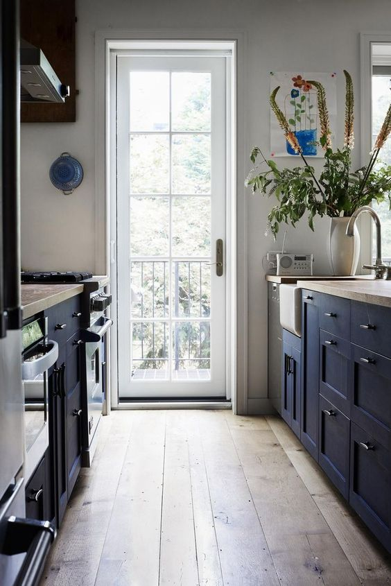 a welcoming navy galley kitchen with wooden countertops, a wooden floor and much natural light coming through the door