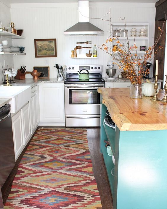 a white traditional kitchen, a colorful boho rug, a blue kitchen island with a wooden countertop with a living edge