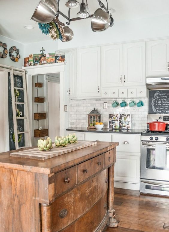 a white traditional kitchen with dark countertops spruced up with a vintage wodoen kitchen island to make it more relaxed