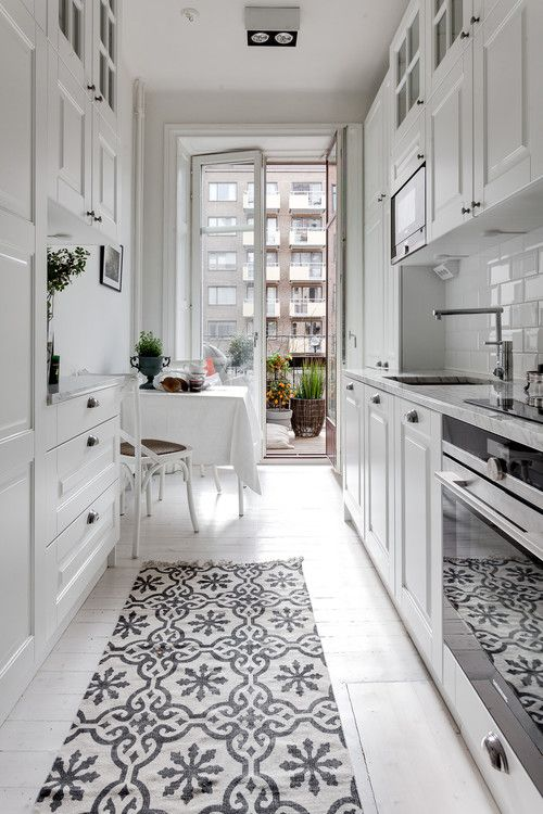 an airy white Scandinavian kitchen with white cabinets, a small dining space by the balcony and a printed rug
