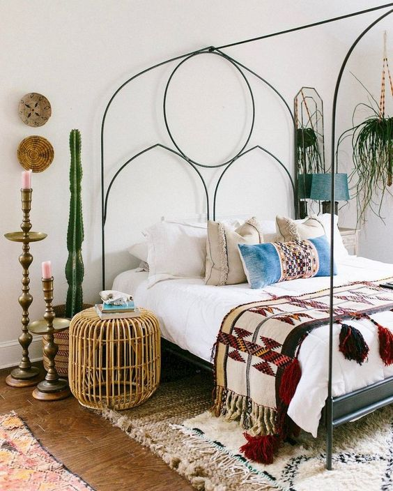 an eclectic bedroom with a metal bed with decor, potted cacti and greenery, a rattan ottoman and vintage candle holders