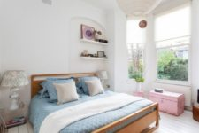 an eclectic bedroom with a modern wooden bed, a pink chest and stool, vintage-inspired lamps and modern built-in shelves