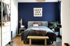 an eclectic bedroom with an upholstered bed, a wicker lampshades, jute and wicker items and a contemporary closet