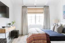 an eclectic bedroom with neutrals and various muted colors, mixed prints and mid-century modern furniture