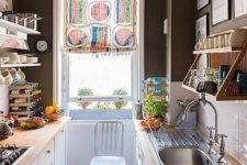 an eclectic galley kitchen with black walls, a checked floor, white cabinets with butcher block countertops and a colorful curtain