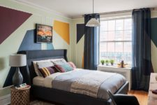an eclectic geometric bedroom with stencils on the wlals, an upholstered black bed, carved stools and nightstands