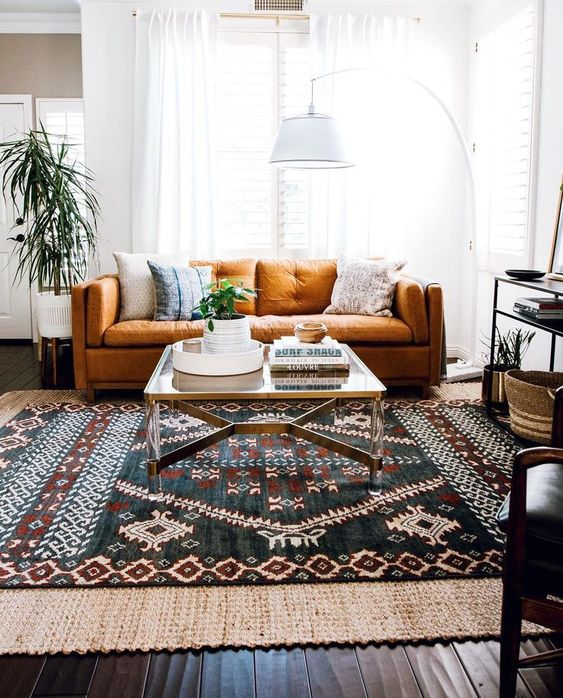 an eclectic living area with a folksy rug, a floor lamp, a rust colored sofa and baskets for storage