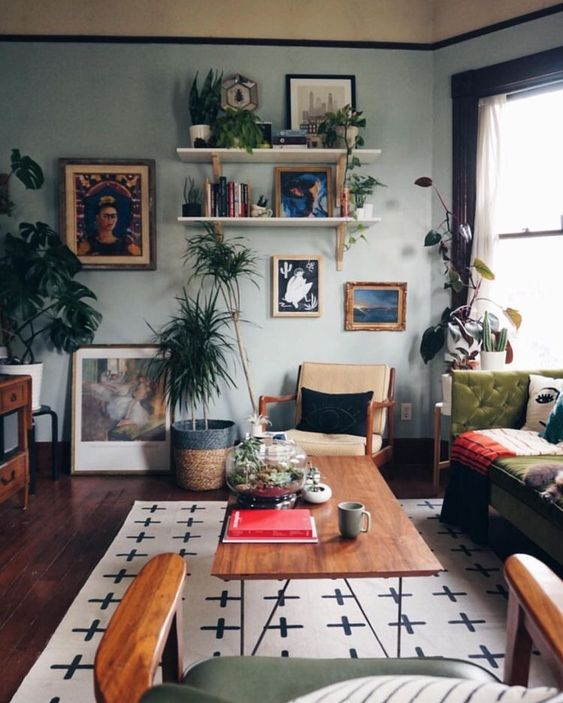 an eclectic living room with a gallery wall, open shelves, light blue walls, vintage furniture and potted greenery
