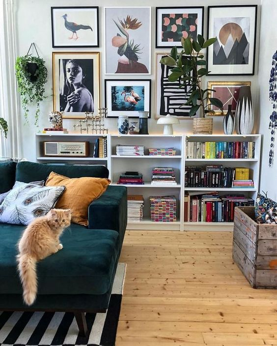 an eclectic living room with open box shelves, a crazy gallery wall, an emrald sof and a striped rug