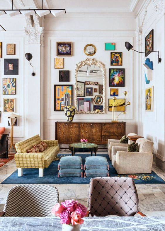 an eclectic living space with a large gallery wall, a vintage mirror, velvet furniture of various colors