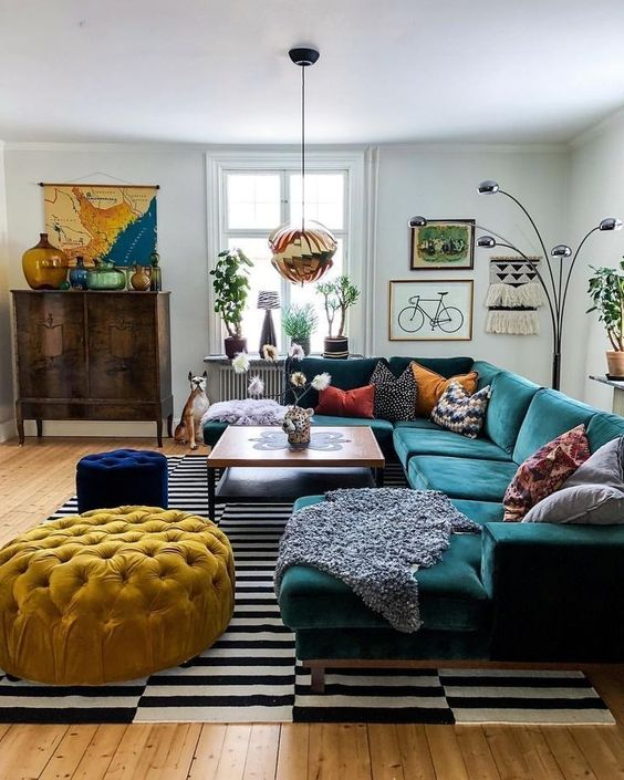an eclectic living space with jewel tone furniture, a striped rug, a gallery wall and a vintage cabinet