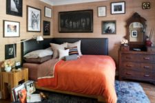an eclectic sleeping space with a dark stained sideboard and mirror, a black leather bed, a rustic nightstand and a huge gallery wall all over