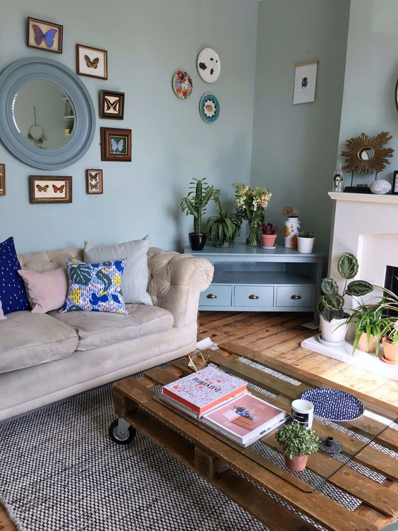 an eclectic space with a pallet coffee table, a neutral sofa unified with light blues and aqua shades