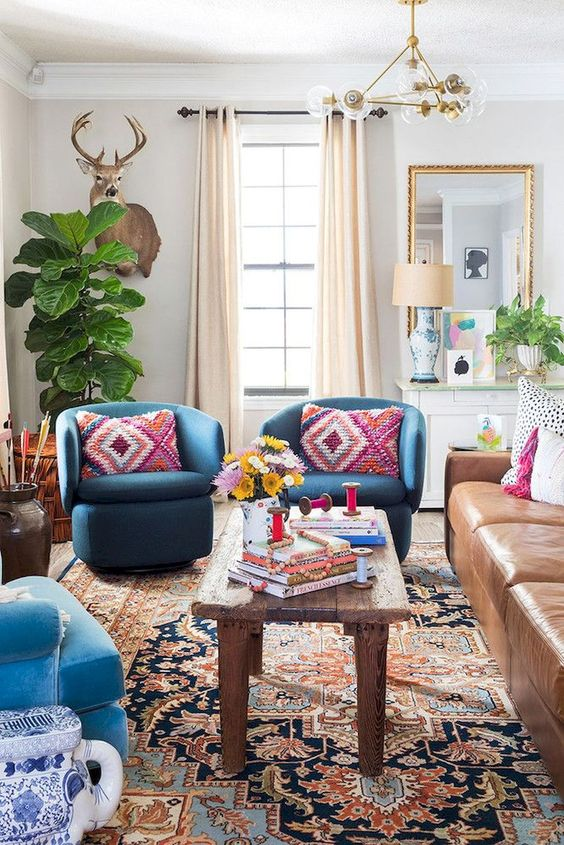 an eclectic space with folksy and boho textiles, a mid-century modern chandelier, a leather sofa and bright blue chairs